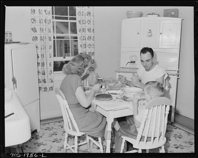 P.C. Goins, section foreman, and family eat dinner in kitchen in their home in company housing project. Koppers Coal Division, Kopperston Mines, Kopperston, Wyoming County, West Virginia.