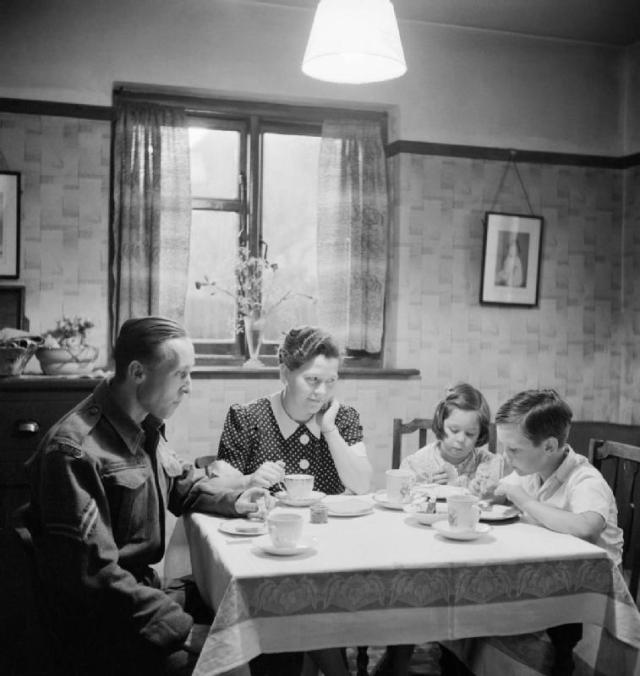 Member of the Home Guard eating tea with his family prior to going on duty, 1942. Richard Sainsbury has tea with his wife and two children, Elaine (6) and David (7). He is dressed in his Home Guard uniform and will be out on duty as soon as he has finished eating.