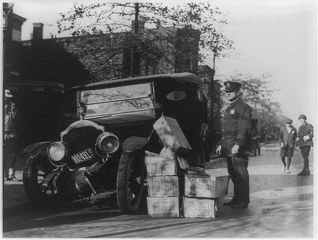 Black-and-white photograph of policeman standing alongside wrecked car and cases of moonshine liquor. Courtesy of the Prints and Photographs Division, Library of Congress, Washington, D. C.