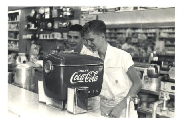 "This is a scene showing the newly installed ""Boat Motor"" styled Coca-Cola soda dispenser just after the dispenser's installation at Fleeman's Pharmacy, Atlanta, Georgia, circa 1948. The legend is that this ""Boat Motor"" styled Coca-Cola dispenser was the first ever of this 1948 model installed anywhere, and in this case was installed in the city where Coca-Cola was created. The pharmacy was originally built in 1914 under the name Atkins Park Pharmacy and in the 1930's became known as Cox & Baucom; all in an era that came to be called ""the golden age of soda fountains."" From its very onset in 1914, the pharmacy began to serve Coca-Cola, and when it closed it's doors in 1995, it had gained the distinction of being the longest running establishment anywhere to have served Coca-Cola - having served Coca-Cola from the same location for eighty-one years straight. Jack Fleeman took over the pharmacy from Messrs. Cox & Baucom. During its existence, Fleeman's Pharmacy became basically the very first Coca-Cola museum, and the walls of the establishment featured rare Coca-Cola artifacts from years past. Some of the Candler family, descendants of Coca-Cola founder Asa Griggs Candler, had been known to sometimes visit with Jack Fleeman over the years, and it has been said that sometimes they would gift Jack Fleeman some old Coca-Cola mementos passed down through the Candler family for his pharmacy museum. The photograph shows two 'soda jerks,' a name given to young teenagers who worked in commercial establishments that served carbonated soda products of years gone by."