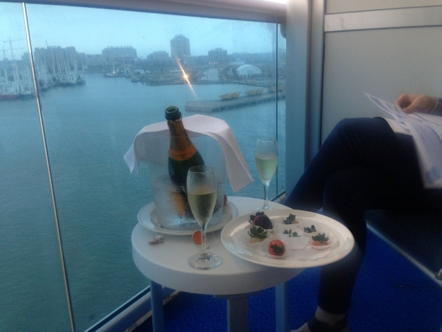 Guests enjoy a bottle of champagne on a private balcony as the ship departs the port in Galveston, Texas.